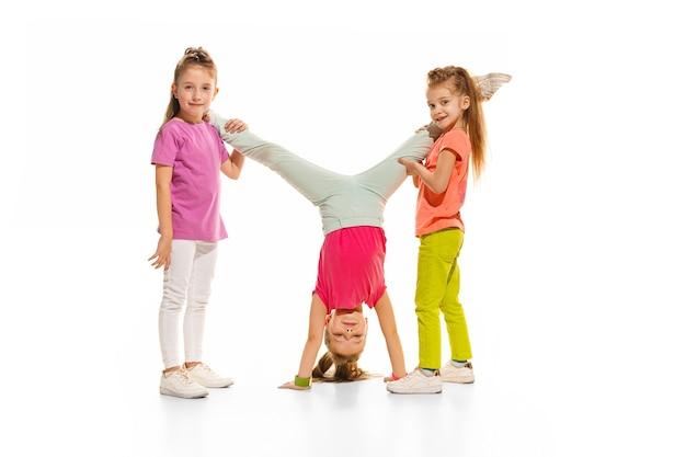 As crianças dançam balé hiphop rua funky e dançarinos modernos no fundo branco do estúdio