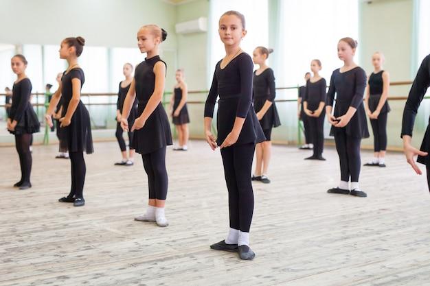 As crianças dançam com um treinador em uma grande sala de treinamento.
