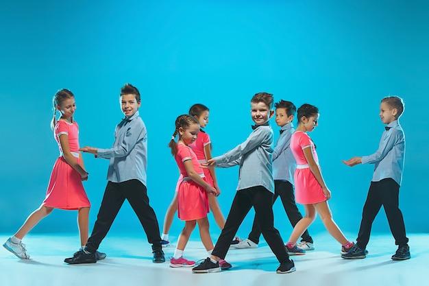 As crianças dançam escola, balé, hiphop, dançarinos de rua, funky e modernos sobre fundo azul do estúdio