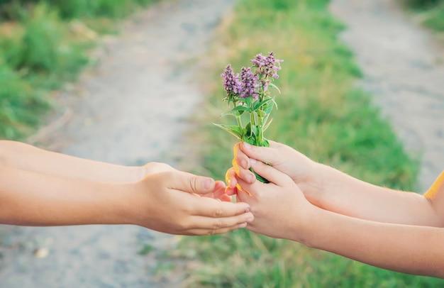As crianças dão as mãos junto com flores