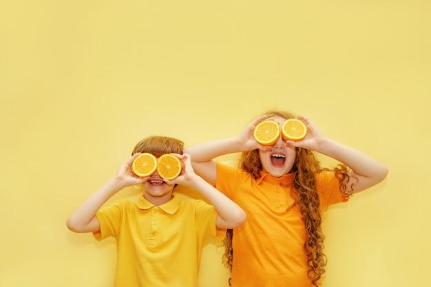 As crianças de riso com olhos alaranjados mostram os dentes saudáveis brancos.