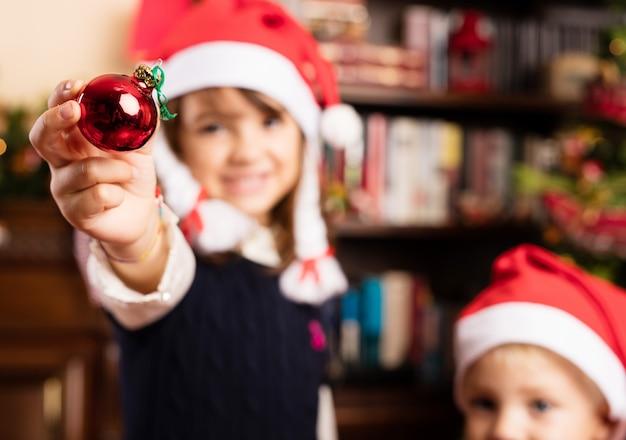 As crianças decoram uma árvore de natal