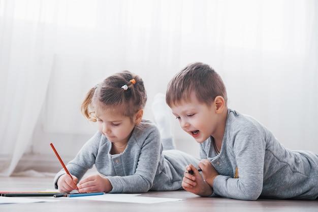 As crianças deitam no chão de pijama e desenham com lápis. pintura bonito da criança por lápis