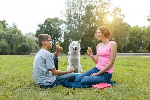 As crianças descansam no parque com um cachorro