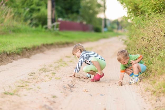 As crianças desenham com uma pedra na areia enquanto se agacham na estrada arenosa de uma aldeia.