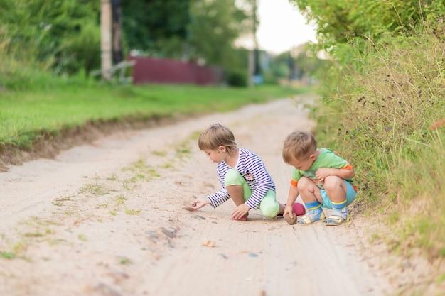 As crianças desenham com uma pedra na areia enquanto se agacham na estrada de uma vila arenosa. foco suave, foco seletivo