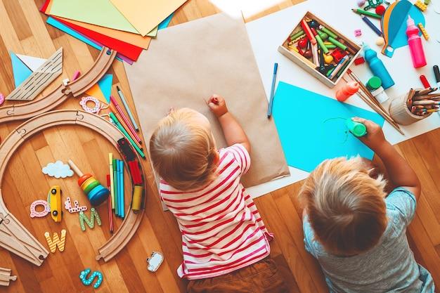 As crianças desenham e fazem artesanato para crianças com brinquedos educativos e material escolar para a criatividade