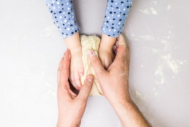 As crianças e as mãos do pai fazem uma massa