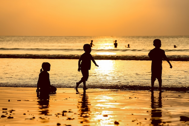 As crianças e o pôr do sol dourado gostam de brincar na praia com o céu de raios de sol