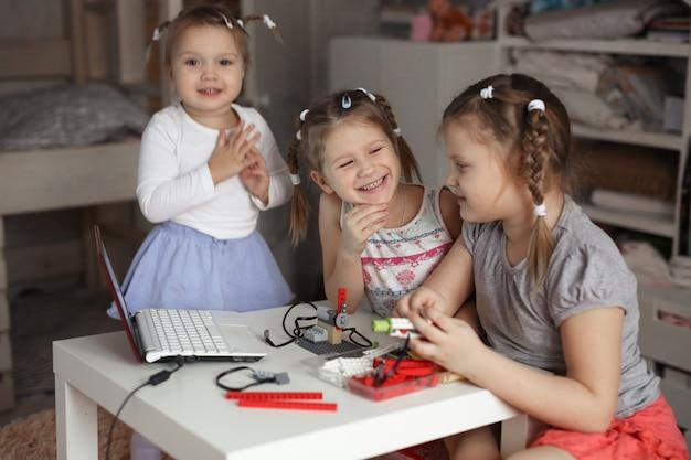 As crianças em casa reúnem robôs, robótica