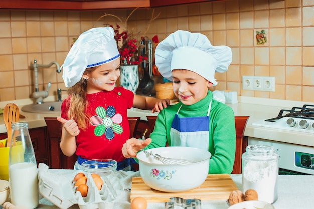 As crianças engraçadas da família feliz estão preparando a massa, assar biscoitos na cozinha