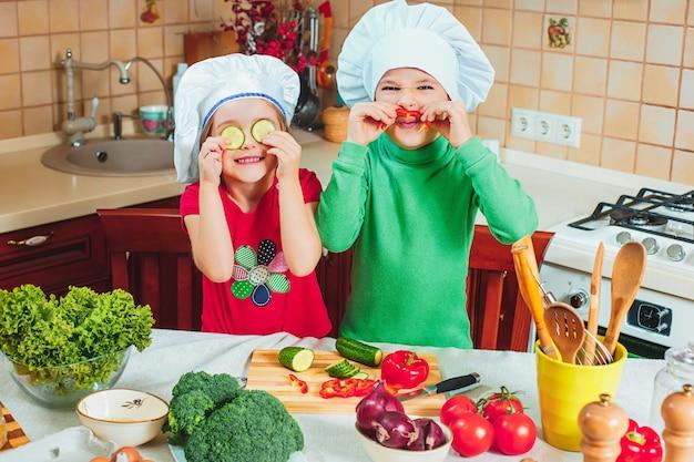As crianças engraçadas da família feliz estão preparando a uma salada de legumes fresca na cozinha