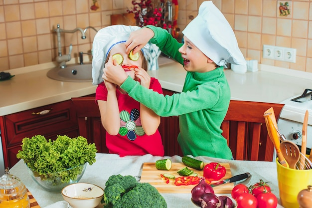 As crianças engraçadas da família feliz estão preparando uma salada de legumes fresca na cozinha