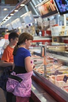 As crianças escolhem produtos no mercado de peixe da suécia, gotemburgo