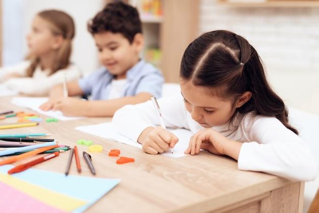 As crianças escrevem em cadernos com uma caneta.