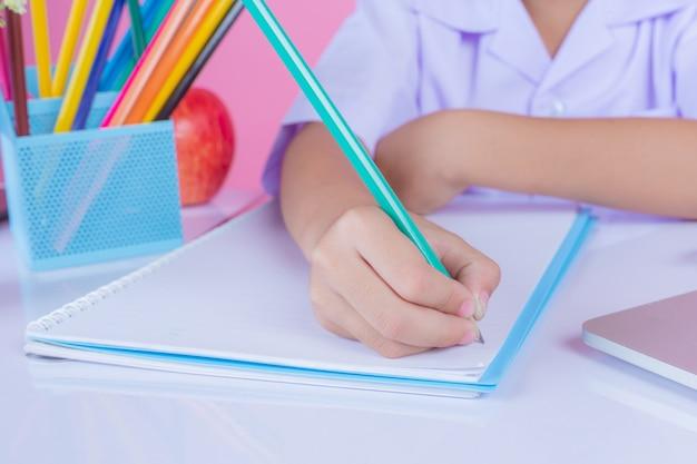 As crianças escrevem gestos do livro em um fundo cor-de-rosa.