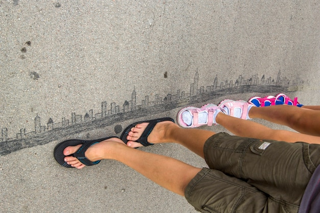 As crianças estão andando na cidade moderna desenhada no asfalto com giz.
