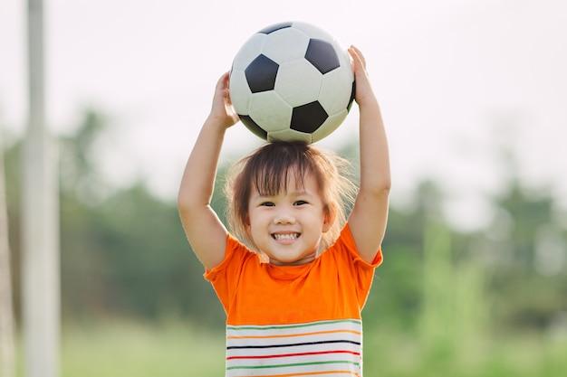 As crianças estão jogando futebol para o exercício sob a luz do sol