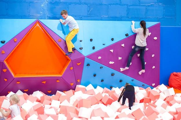 As crianças estão pulando de um trampolim no shopping enquanto os pais estão fazendo compras