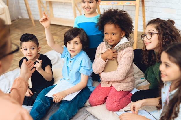 As crianças estão puxando as mãos para responder à pergunta do professor.