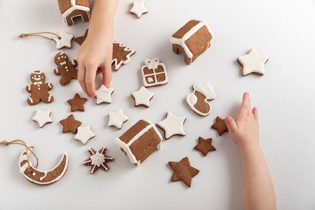 As crianças estão se preparando para o natal. biscoitos de gengibre com cobertura de açúcar nas mãos das crianças. vista do topo.