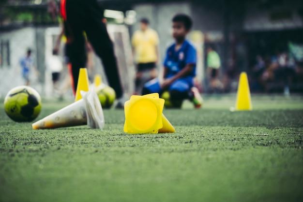 As crianças estão treinando em um campo de futebol em uma academia de futebol com equipamento.