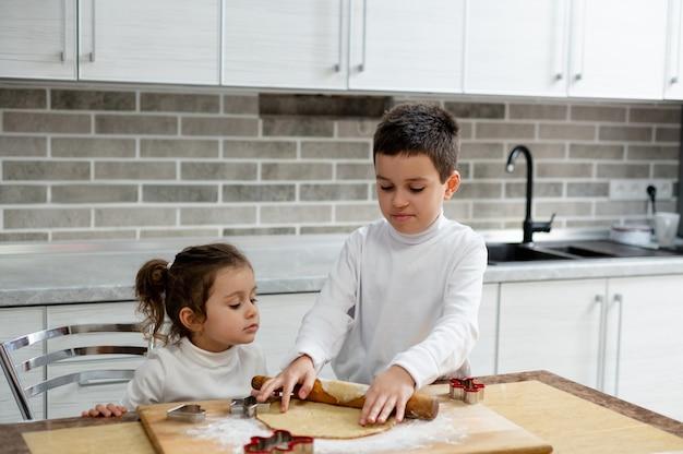 As crianças fazem biscoitos de natal e o menino abre a massa com um rolo de massa