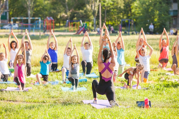 As crianças fazem yoga com um treinador ao ar livre.
