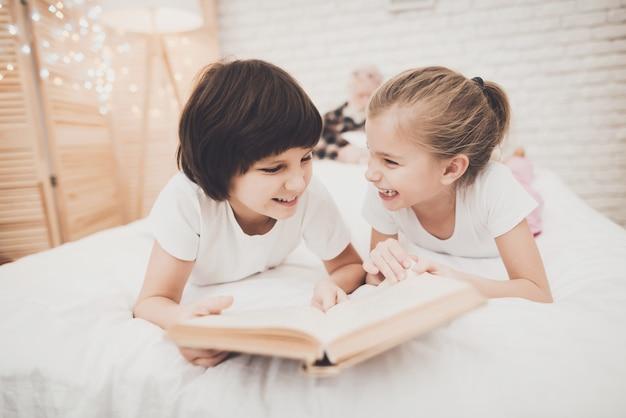 As crianças felizes impertinentes leram o livro quando o vovô dormir.