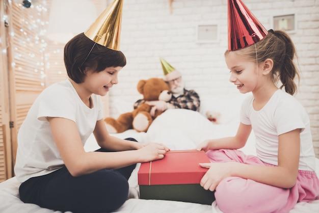 As crianças impertinentes abrem o presente de aniversário que o vovô dorme.