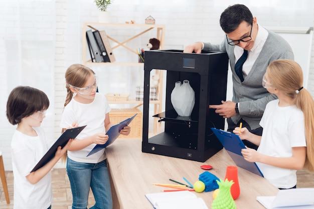 As crianças imprimem artigos diferentes na impressora 3d com um professor.
