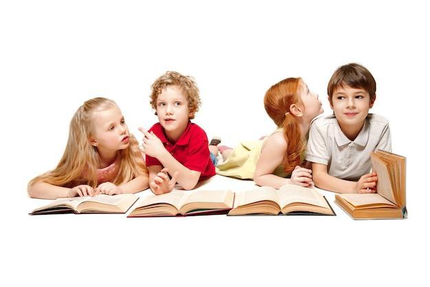 As crianças, menino e menina, deitado com os livros no estúdio, sorrindo, rindo, isolado no branco