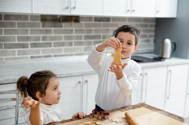 As crianças mostram as formas da massa cortada por elas