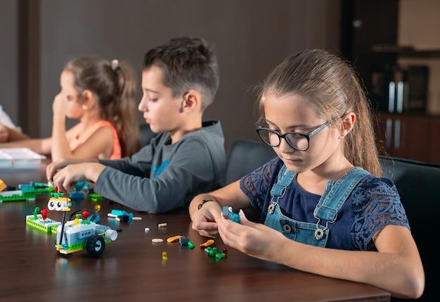 As crianças na sala de aula colecionam figuras do designer.