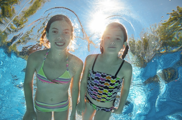 As crianças nadam debaixo d'água na piscina, felizes meninas ativas se divertem debaixo d'água, crianças fitness e esporte em férias em família ativas