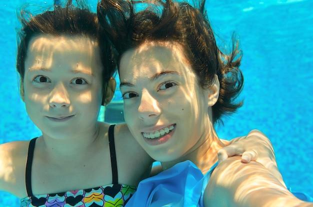 As crianças nadam na piscina debaixo d'água, fazendo selfie, felizes meninas ativas se divertem, crianças esporte em férias em família