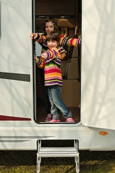 As crianças no campista se divertem, viajam em família no motorhome em férias no acampamento