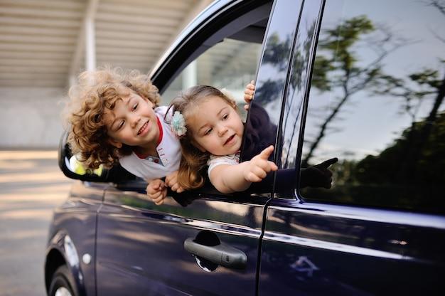 As crianças olham para fora de uma janela de carro