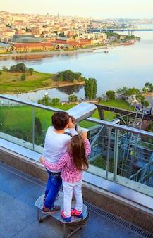 As crianças olham para istambul através de binóculos ao pôr do sol na istambul