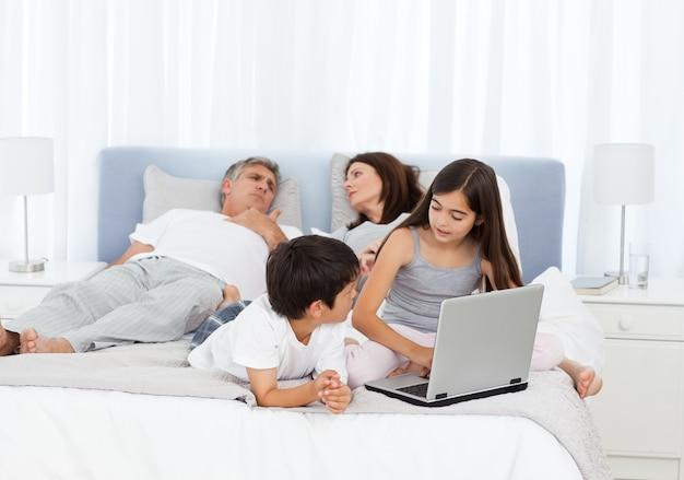 As crianças olham para o laptop enquanto os pais falam