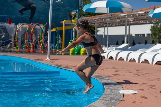 As crianças passam as férias no parque aquático, uma menina feliz fugiu e pula do lado do granito para o ...