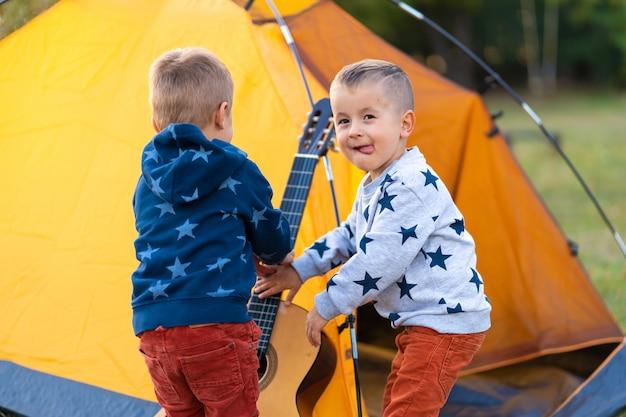 As crianças pedem ao pai para tocar violão. acampar com a família na floresta. feliz fim de semana em família
