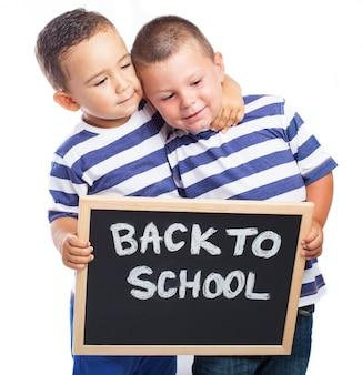 As crianças pequenas, abrangendo um quadro-negro com a mensagem