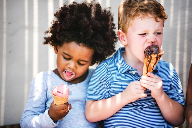 As crianças pequenas comendo sorvete gostoso