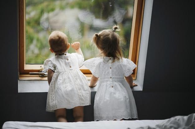 As crianças pequenas estão olhando curiosamente a janela