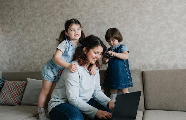 As crianças pequenas impedem a mãe de trabalhar no computador. trabalho remoto em casa