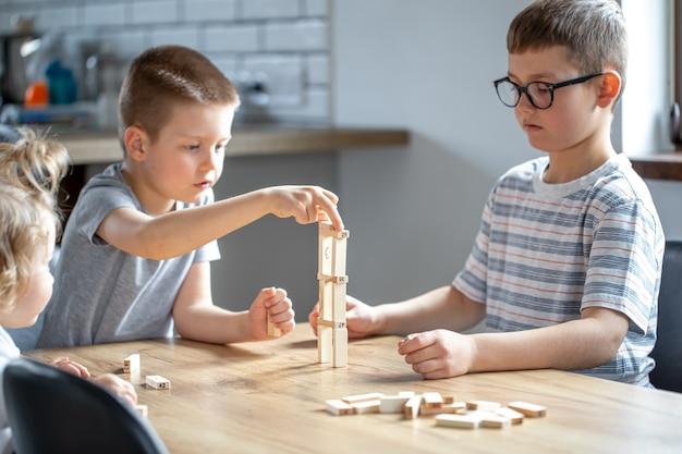 As crianças pequenas jogam um jogo de tabuleiro com cubos de madeira em casa na cozinha.