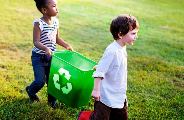 As crianças pequenas que separam recicl podem ao caixote de lixo