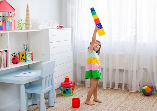 As crianças prées-escolar felizes da idade jogam com blocos plásticos coloridos do brinquedo.