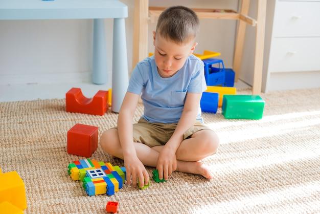 As crianças prées-escolar felizes jogam com blocos do brinquedo.